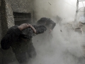Run for cover: Free Syrian Army fighters run for cover as a tank shell explodes on a wall during heavy fighting in the Ain Tarma neighbourhood of Damascus on January 30.