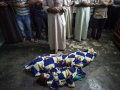 Inhumane: Family members on July 13 prayed over the bodies of two Syrian children, Safia Baour, 14, and her three-year-old brother Khaled, who were killed after a shell landed on their home as they gathered for Iftar in Maaret Al-Numan in southern Idlib province, Syria.
