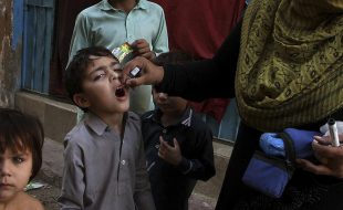 A Pakistani health worker gives a polio vaccine to a child in Karachi, Pakistan, Thursday, Dec. 1, 2016. Polio remains endemic in Pakistan after the Taliban banned vaccinations, instigated attacks targeting medical staffers and spread suspicions about the vaccine. (AP Photo/Fareed Khan)